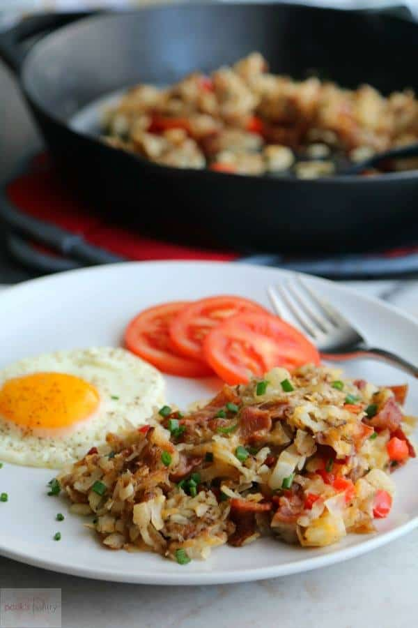 Crispy, Cheesy Hash Browns from Pook's Pantry on a plate with an over easy egg and sliced tomatoes