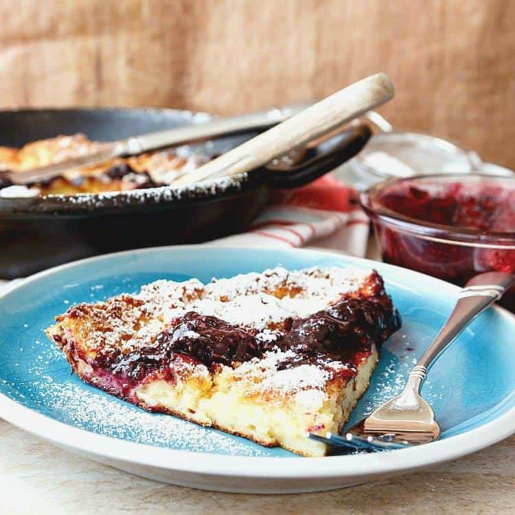 A German Pancakes/Dutch Baby from Pastry Chef Online sits on a turquoise plate, topped with jam, before eating.