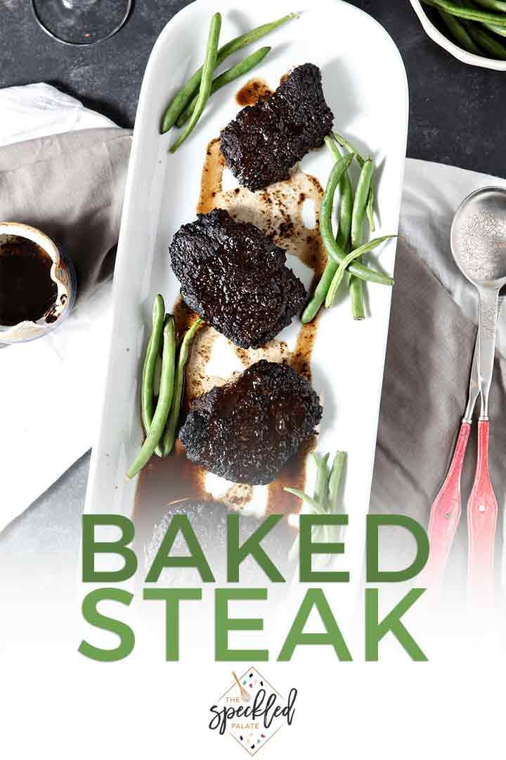 Overhead of Baked Steak on a platter with green beans and Pinterest text
