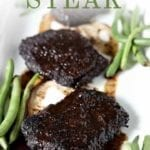 Close up of Baked Steak on a platter with green beans and Pinterest text