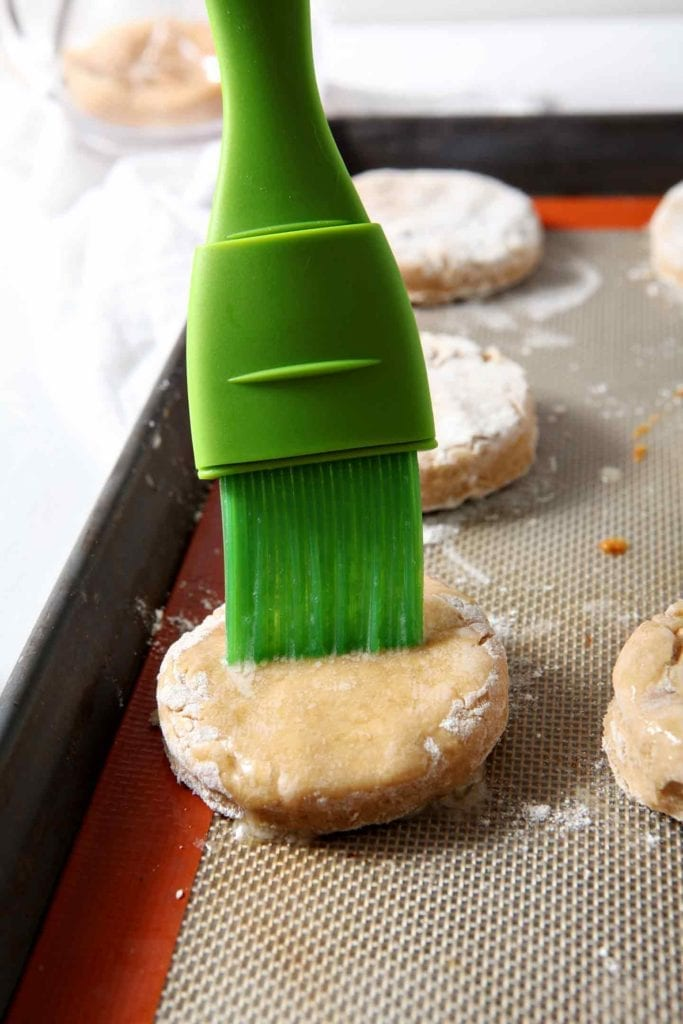 A green pastry brush brushes butter onto a biscuit on a baking sheet