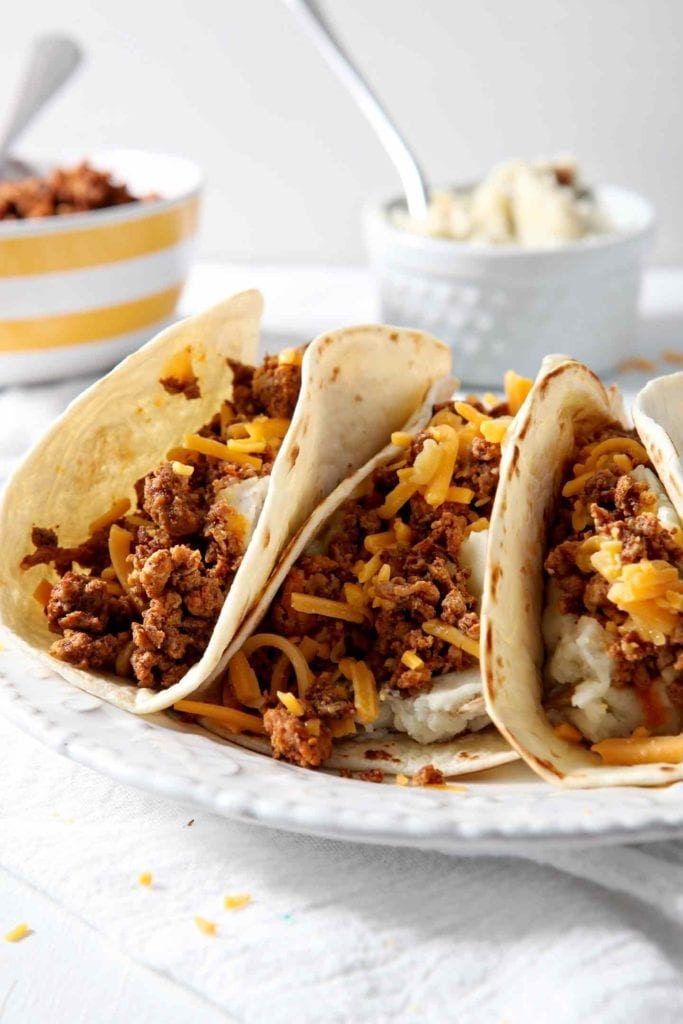 One white plate holding three Mashed Potato Chorizo Breakfast Tacos ready for eating on a white background