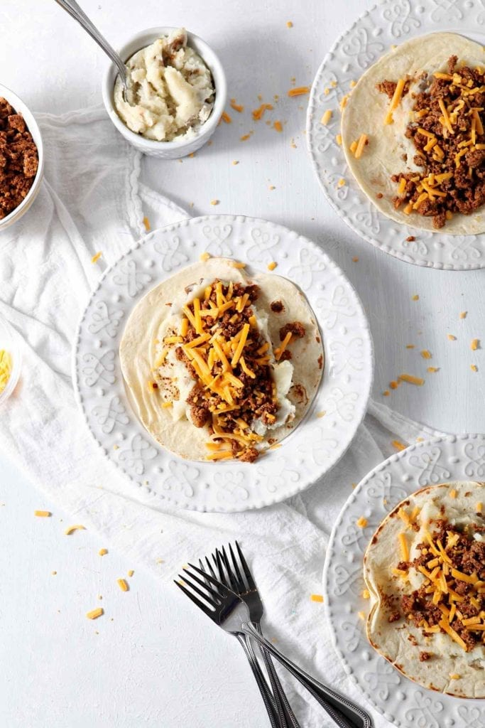 Three white plates holding prepared Mashed Potato Chorizo Breakfast Tacos from above