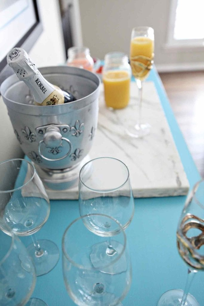 A bar is set up on a turquoise piece of furniture, complete with glassware on display, champagne in an ice bucket and more