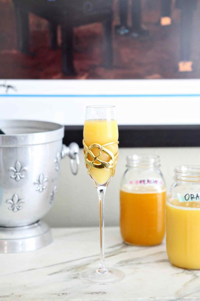 A bellini (a champagne and peach juice cocktail) sits on a marble slab, surrounded by jars holding other juices and champagne