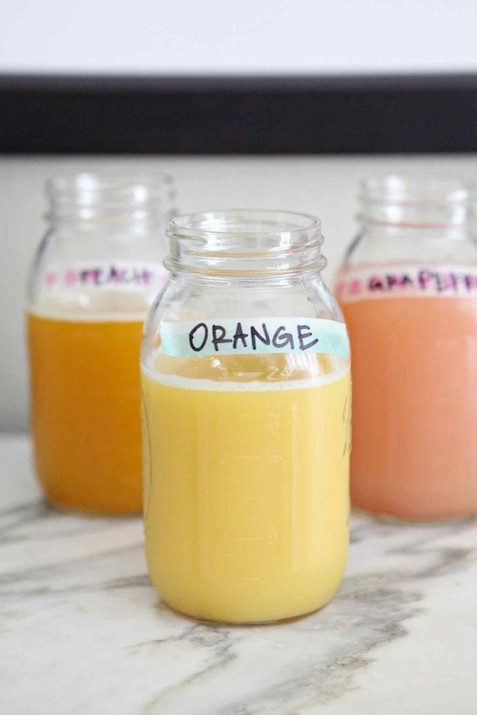 Juices, served in mason jars and labeled with washi tape, are set out for guests