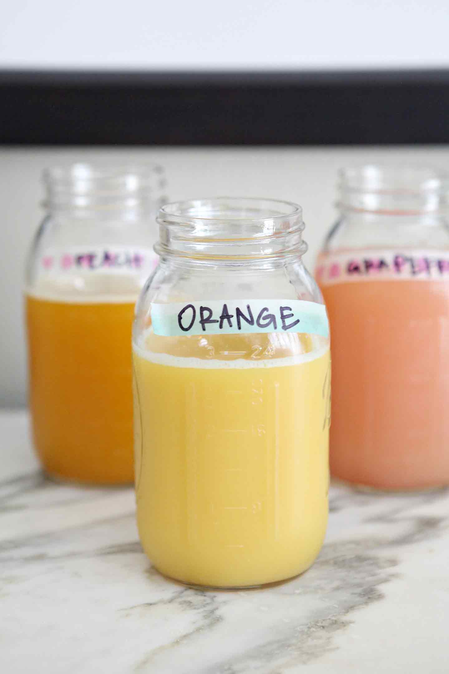 Juices, served in mason jars and labeled with washi tape, are displayed on a turquoise breakfast bar as a part of the Mimosa Bar