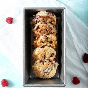 Raspberry Shortcake Biscuits are displayed in a metal loaf pan while sitting on a turquoise surface and a white flour sack towel with raspberries scattered about.