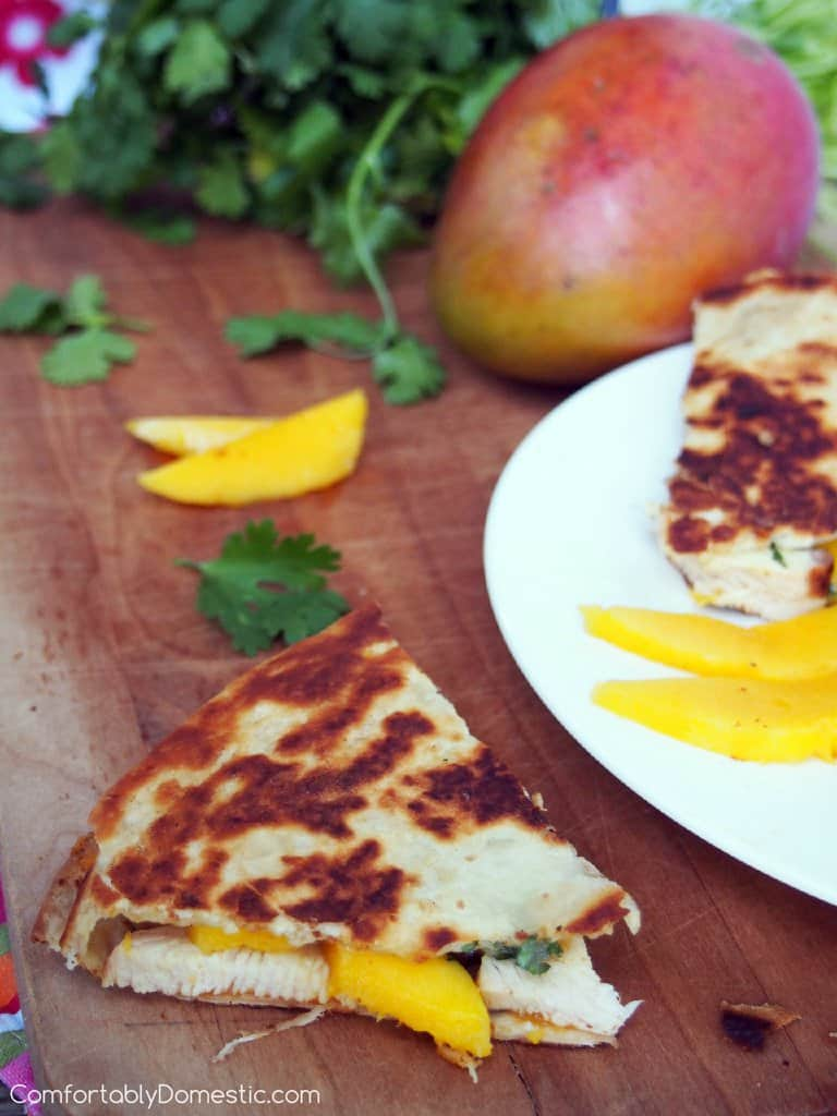 Toasty Chicken and Mango Brie Quesadillas on a wooden cutting board