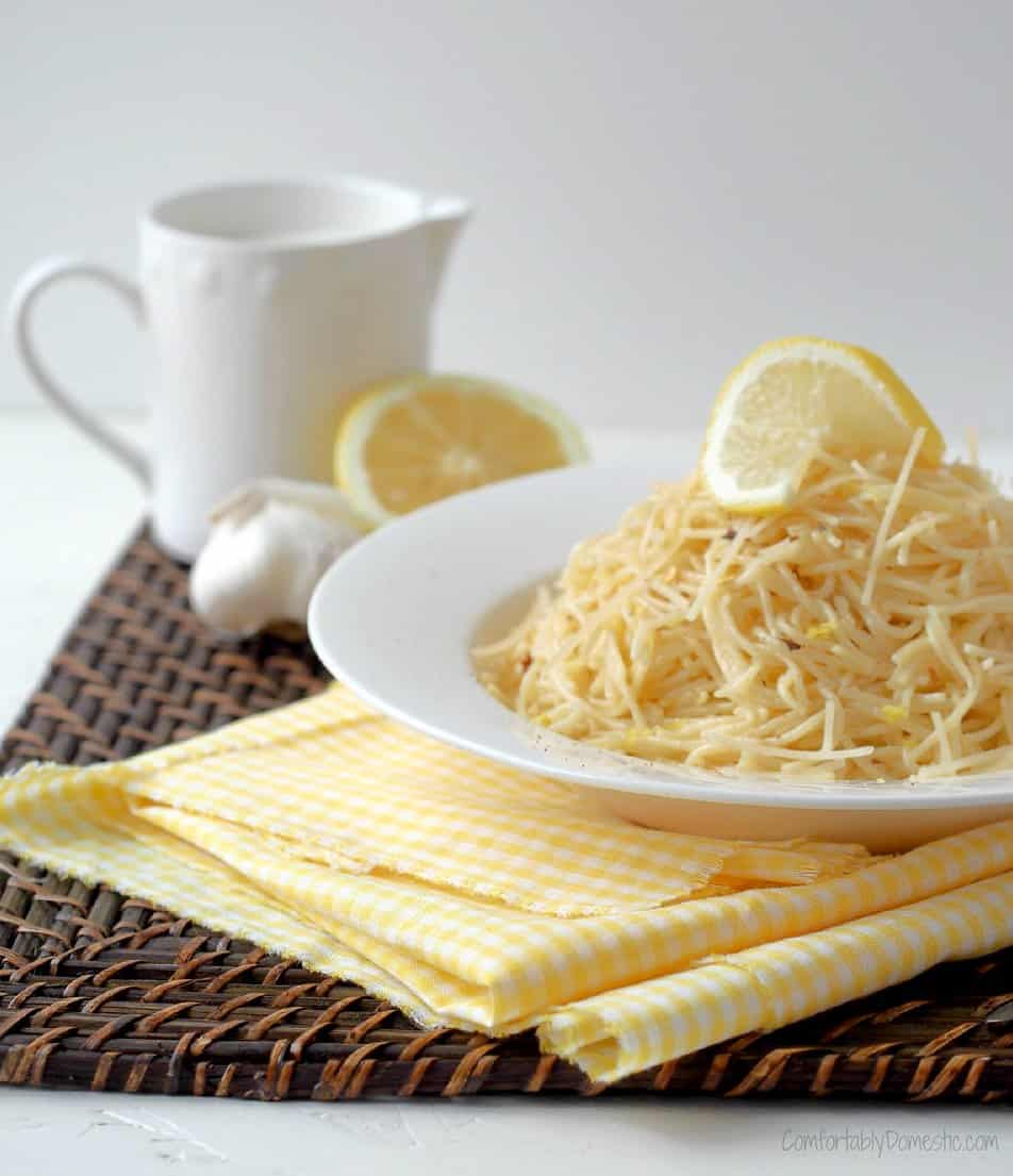 Easy Lemon Cream Pasta from Comfortably Domestic on a white plate with a yellow napkin and lemon rounds
