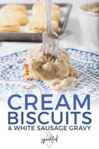 A fork cuts into a Cream Biscuit, topped with White Sausage Gravy, with Pinterest text