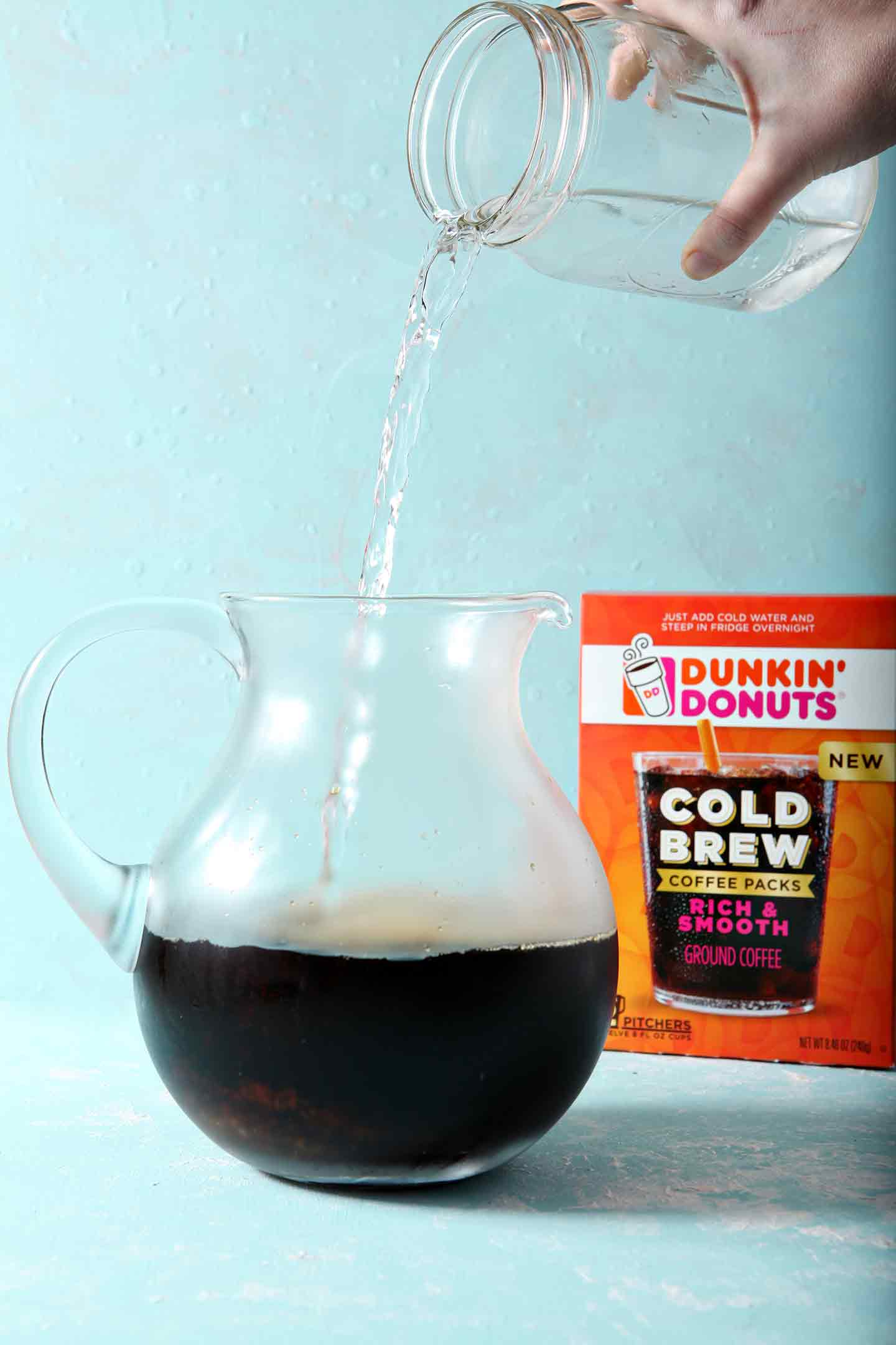 Water being poured on top of Dunkin' Donuts Cold Brew packets, on a turquoise background, before going in the fridge to steep overnight