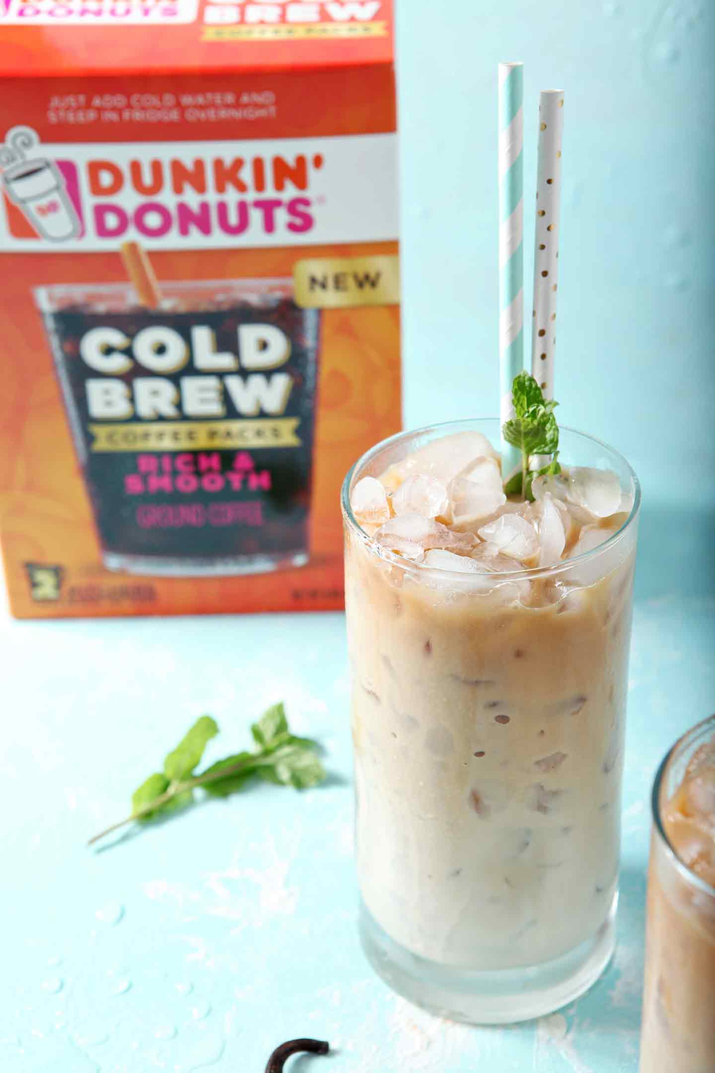 One glass of Dunkin' Donuts Cold Brew with Homemade Vanilla Mint Creamer, on a turquoise background, ready for drinking, with the Dunkin Donuts Cold Brew package in the background