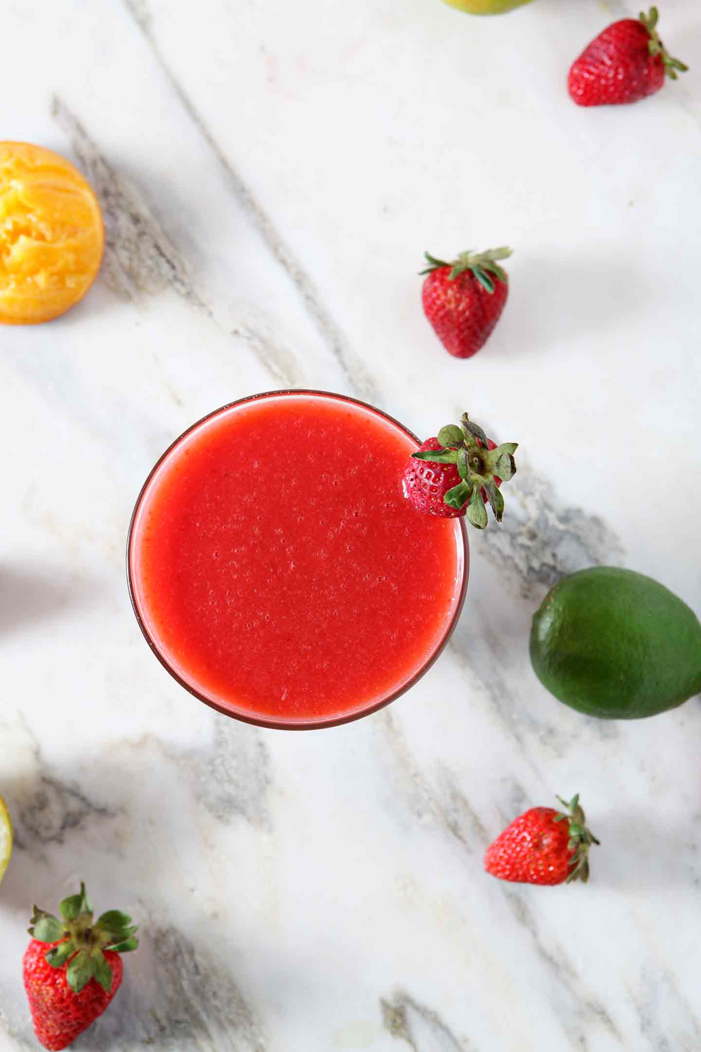 A Strawberry Virgin Margarita sits on a marble background, surrounded by strawberries, limes and oranges.