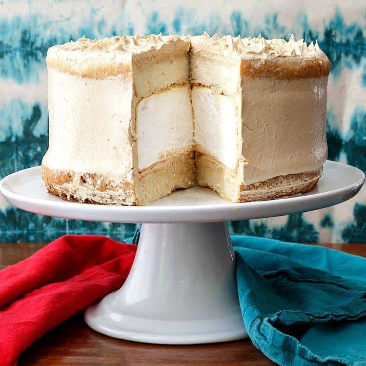 Peanut Butter Marshmallow Cake from Pastry Chef Online, shown on a white cake platter, with a turquoise background