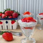 Strawberries and Cream Chia Pudding are served in parfait glasses and topped with fresh strawberries