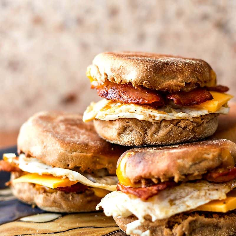 A platter, stacked high with Whole Wheat English Muffins (for Bacon, Egg & Cheese Sammiches) from Pastry Chef Online, is served.