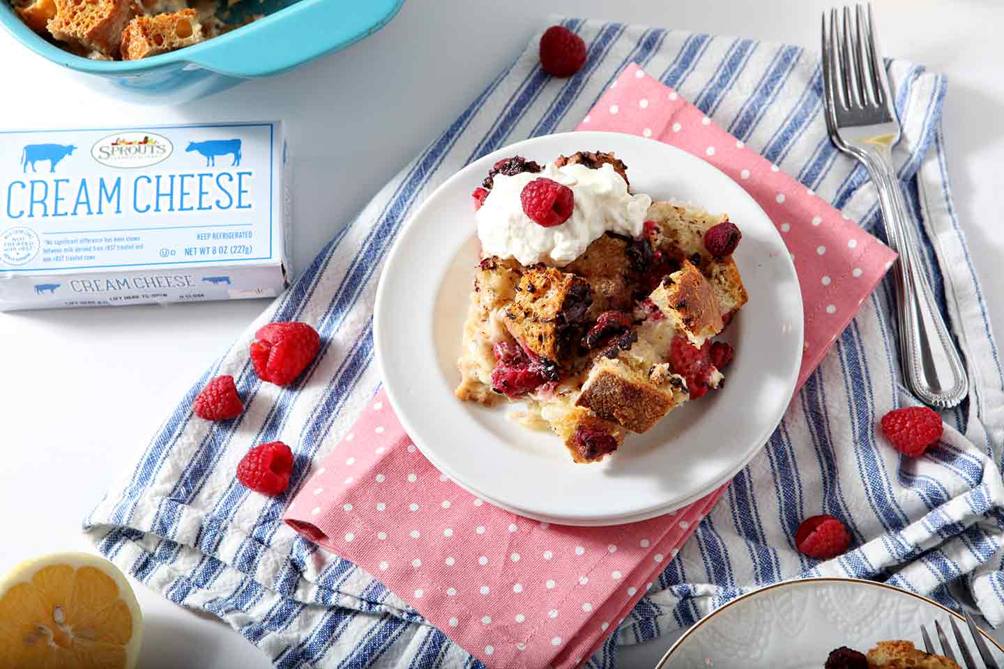 Horizontal image of Chocolate Raspberry Overnight French Toast Casserole, served on a white plate and topped with whipped cream and raspberries, on a white surface on top of blue and pink kitchen towels
