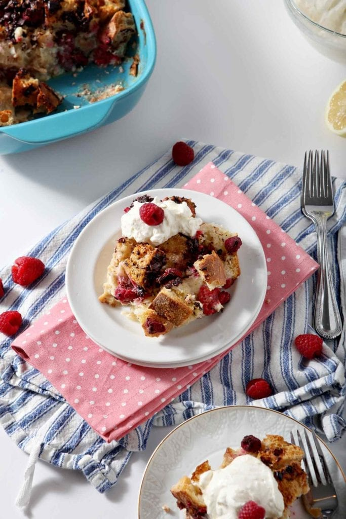 Two plates of Chocolate Raspberry Overnight French Toast Casserole are shown on a white background, ready for eating and topped with Lemon Whipped Cream