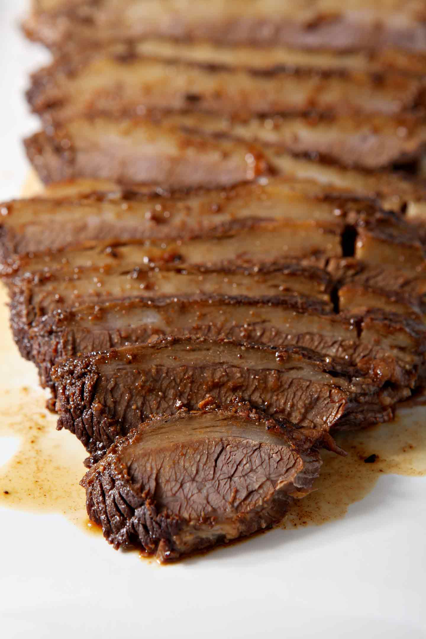 Close up photo of sliced Instant Pot BBQ Brisket on a white platter, surrounded by juices