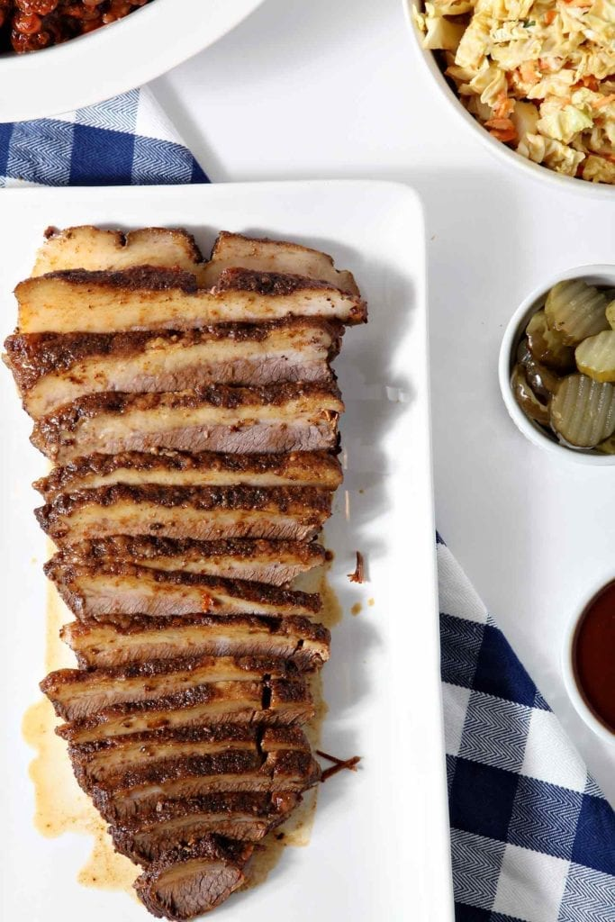 Overhead image of Instant Pot BBQ Brisket, served on a white platter, with pickles, barbecue sauce, coleslaw and baked beans