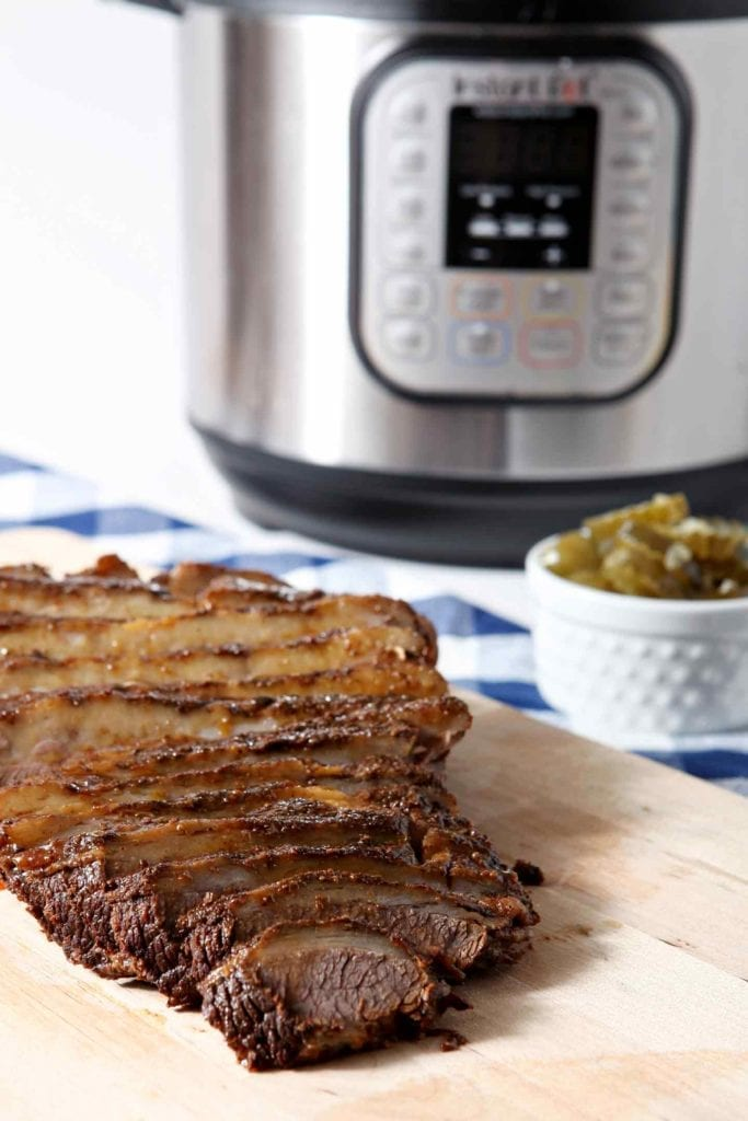 Instant Pot BBQ Brisket sits on a wooden cutting board in front of an Instant Pot after cooking and slicing.