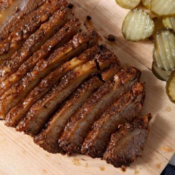 Overhead image of Instant Pot BBQ Brisket, shown on a wooden cutting board, served with barbecue sauce and pickles