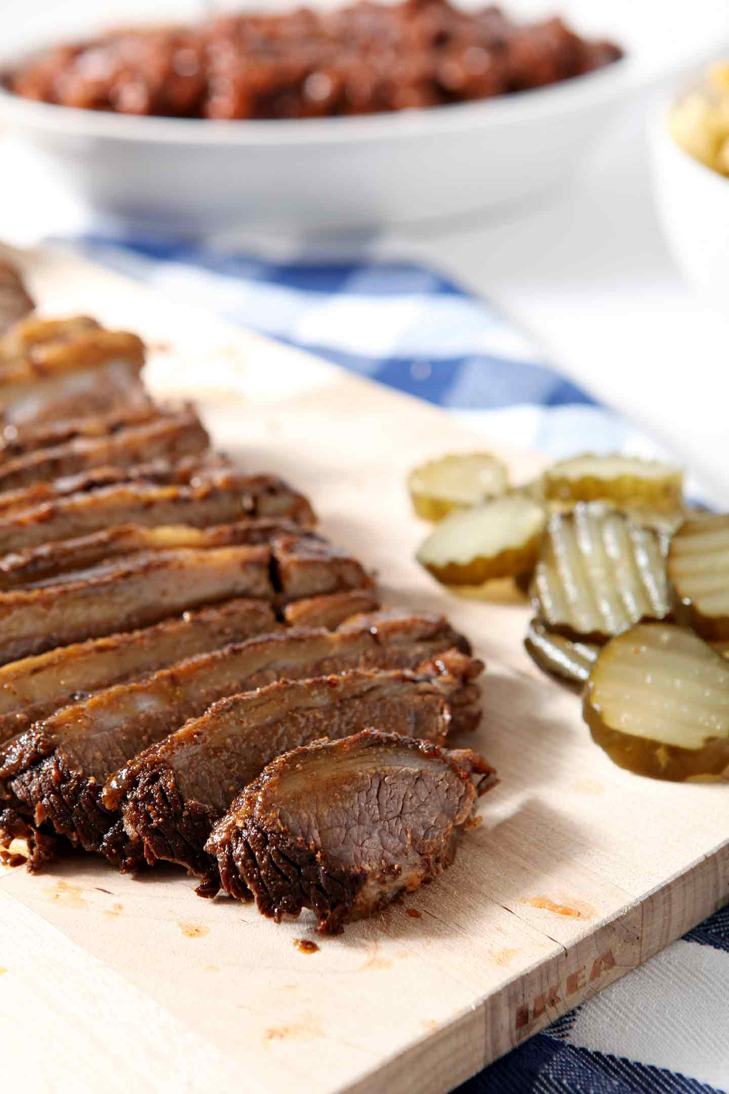 Sliced Instant Pot BBQ Brisket sits on a wooden cutting board with pickles and is served with baked beans, as shown in the background.