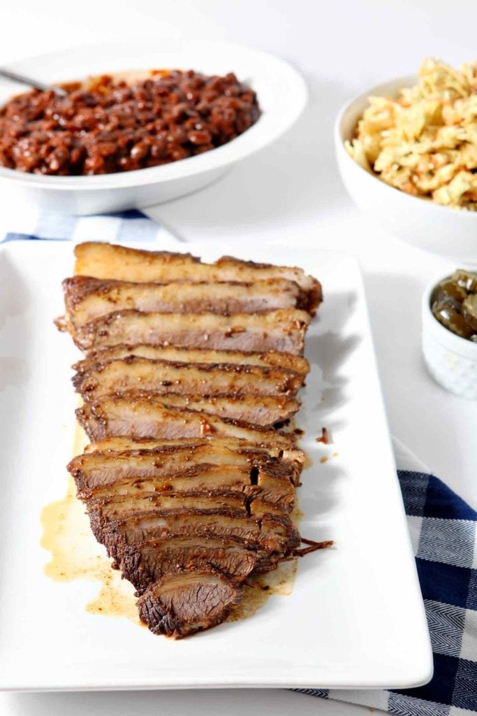 Instant Pot BBQ Brisket, served on a white platter, surrounded by barbecue sides like coleslaw, baked beans, pickles and barbecue sauce.