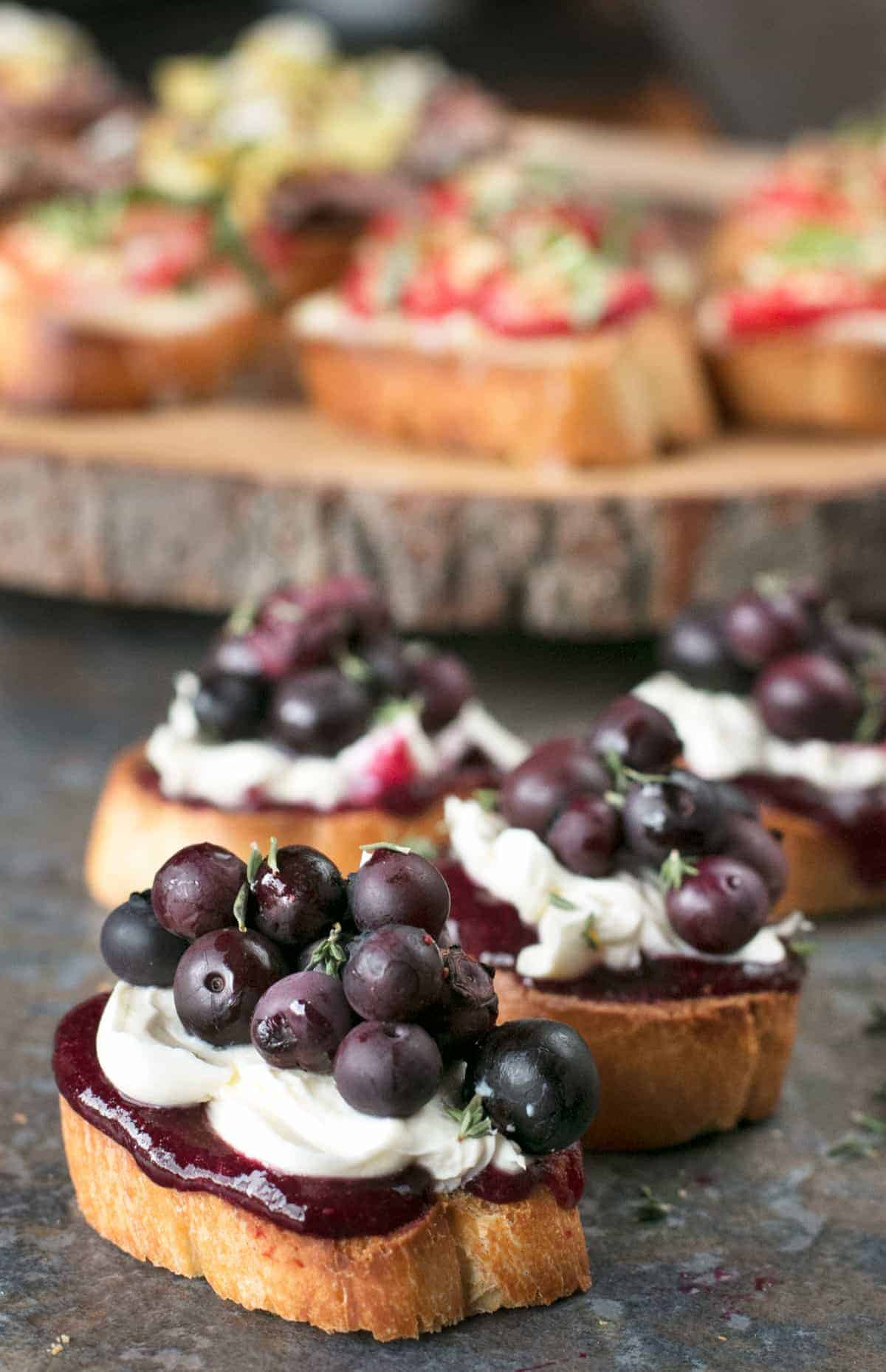 Several Blueberry Thyme Mascarpone Crostini sit in front of a wooden round that holds more summertime crostini