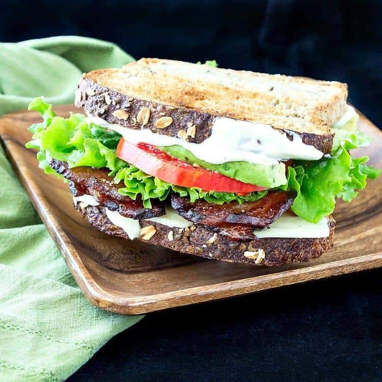 A Gourmet BLT with Cheddar and Avocado is shown on a bamboo platter with a green cloth napkin on a dark background