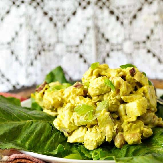 Coronation Chicken (Curried Chicken Salad) is served on a green lettuce leaf with a patterned background
