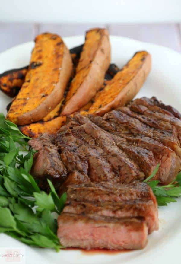 Espresso Bourbon Steak and Grilled Sweet Potatoes are served on a white plate with greens