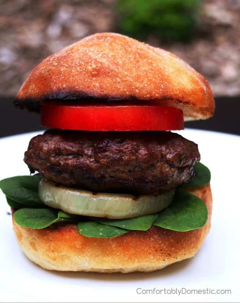 A Feta Stuffed Lamb Burger sits on a white plate, layered with spinach, onion and tomato.