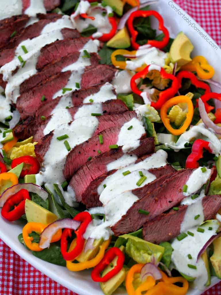 A bowl of Grilled Steak Salad with Chive Yogurt Dressing (from Comfortably Domestic) is shown in close up