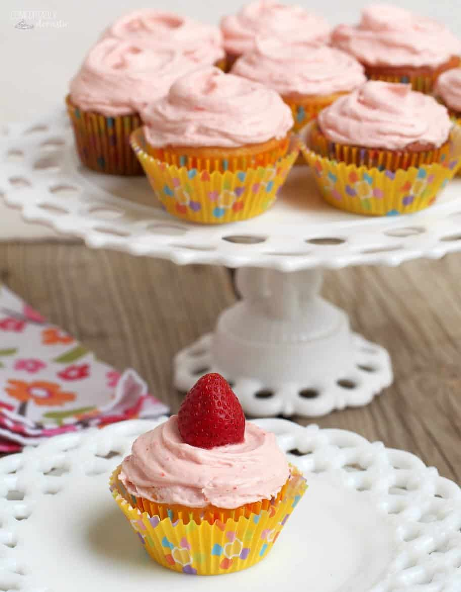 One Lemonade Cupcakes with Fresh Strawberry Buttercream is displayed on a white plate while others sit on a cake stand