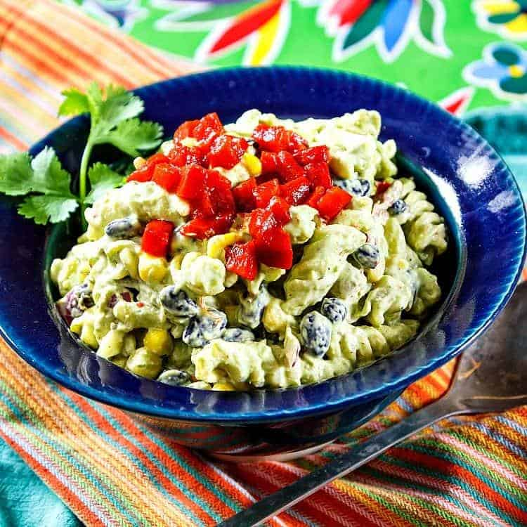A bowl of Mexican Green Goddess Pasta Salad, shown in blue pottery, is served on a colorful background with a spoon.