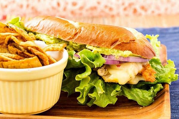 Pastry Chef Online's Spicy Chicken Guacamole Sandwich sits on a wooden cutting board and is served with chips