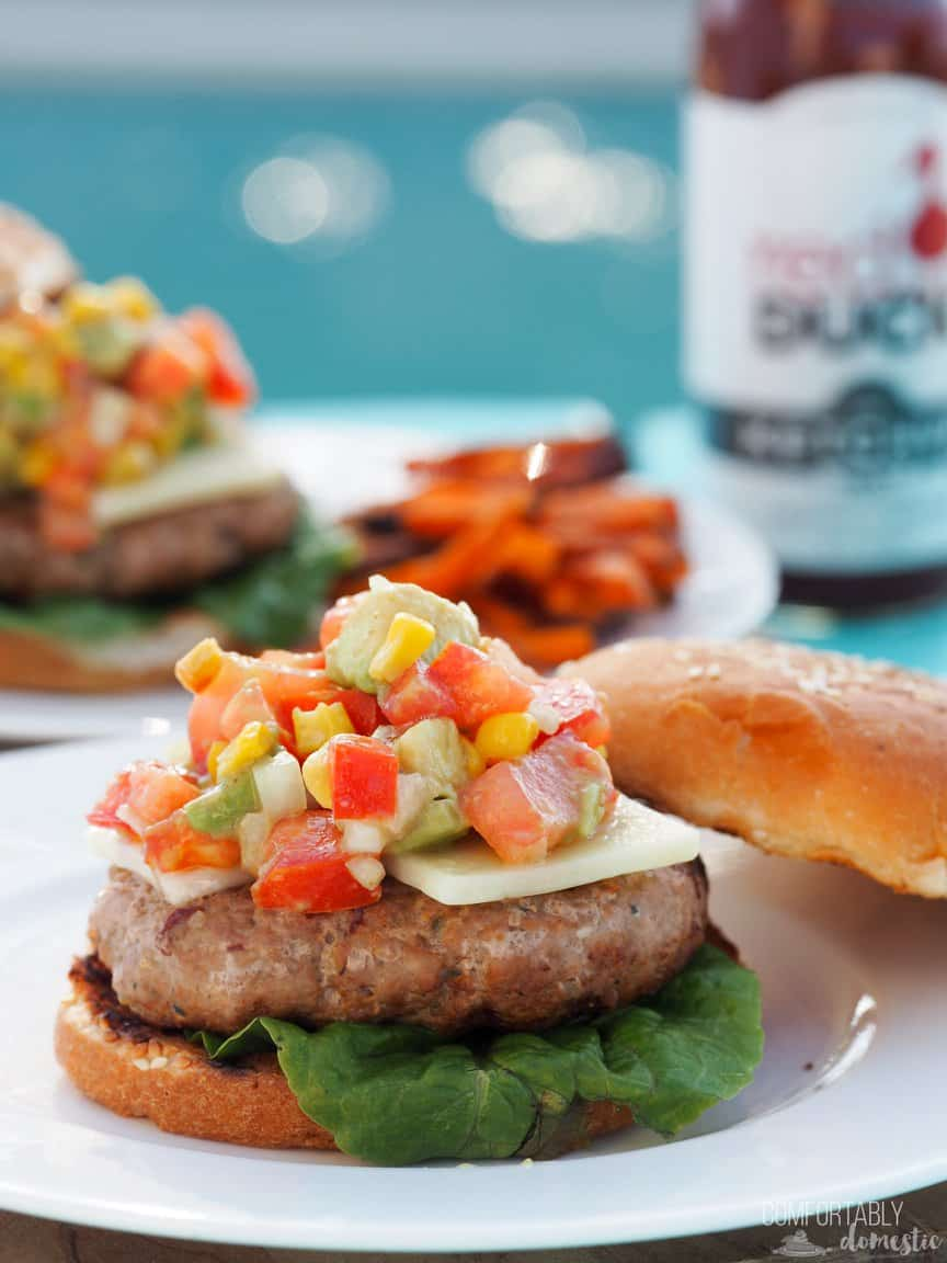 A Spicy Chipotle Turkey Burger with Corn and Avocado Salsa sits on a white plate with other burgers and sides in the background