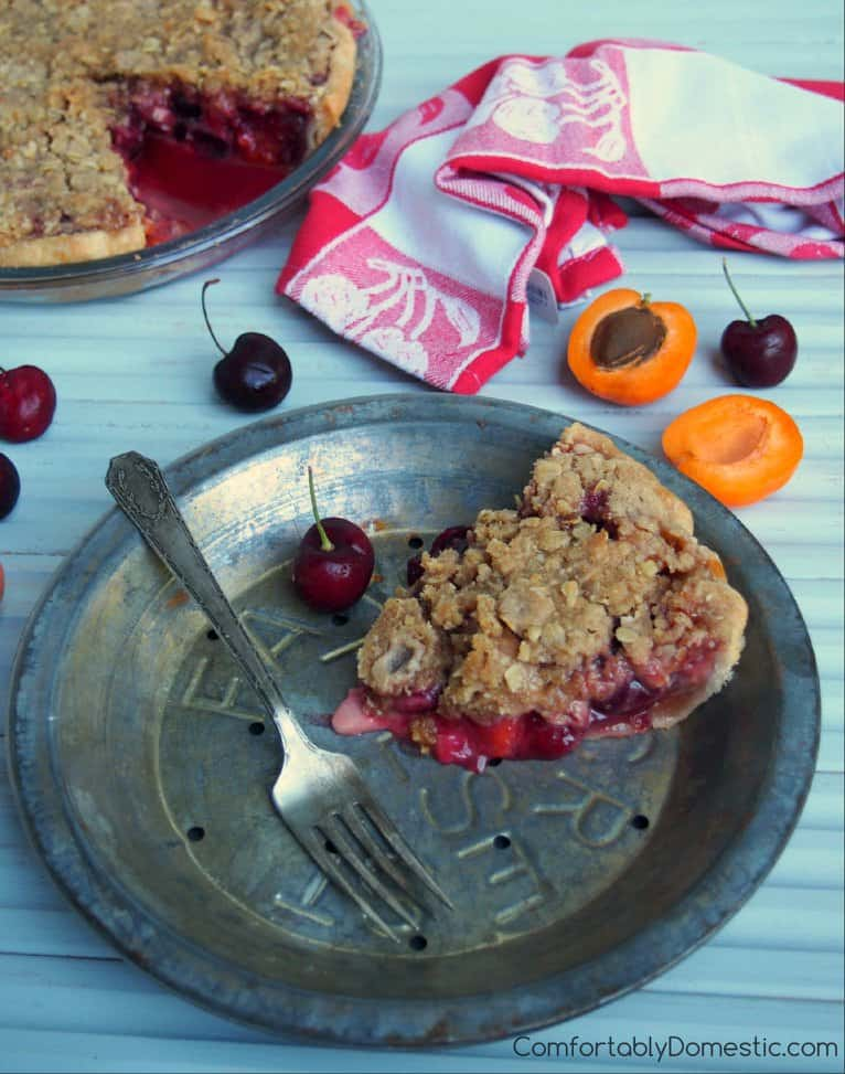 A pewter platter serves a slice of Sweet Cherry Apricot Crumb Pie, surrounded by fresh cherries and apricots, as well as the whole pie in the background