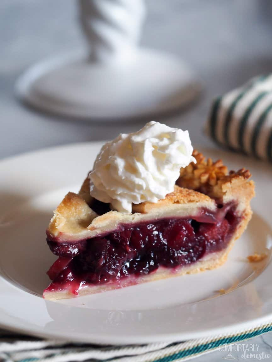 A slice of Sweet Cherry Rhubarb Pie, shown with whipped cream on top, sits on a white plate in a diner setting.