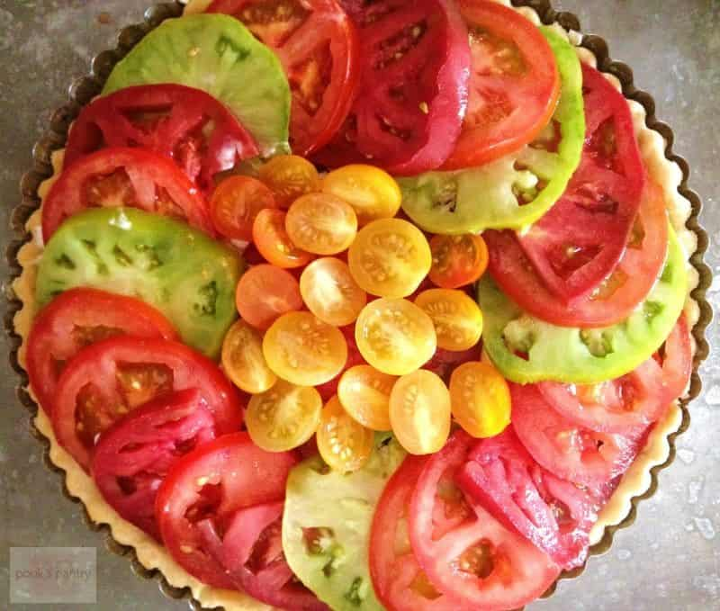 Overhead image of a Tomato and Goat Cheese Tart, featuring red, green and yellow tomatoes.