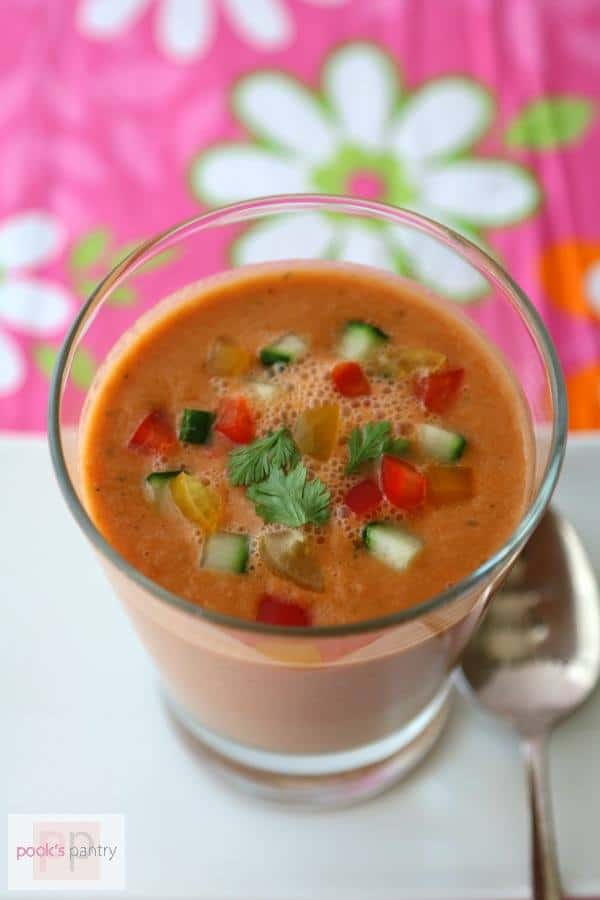 A cup of Watermelon Gazpacho is garnished with watermelon, cucumber and herbs while sitting on a white platter