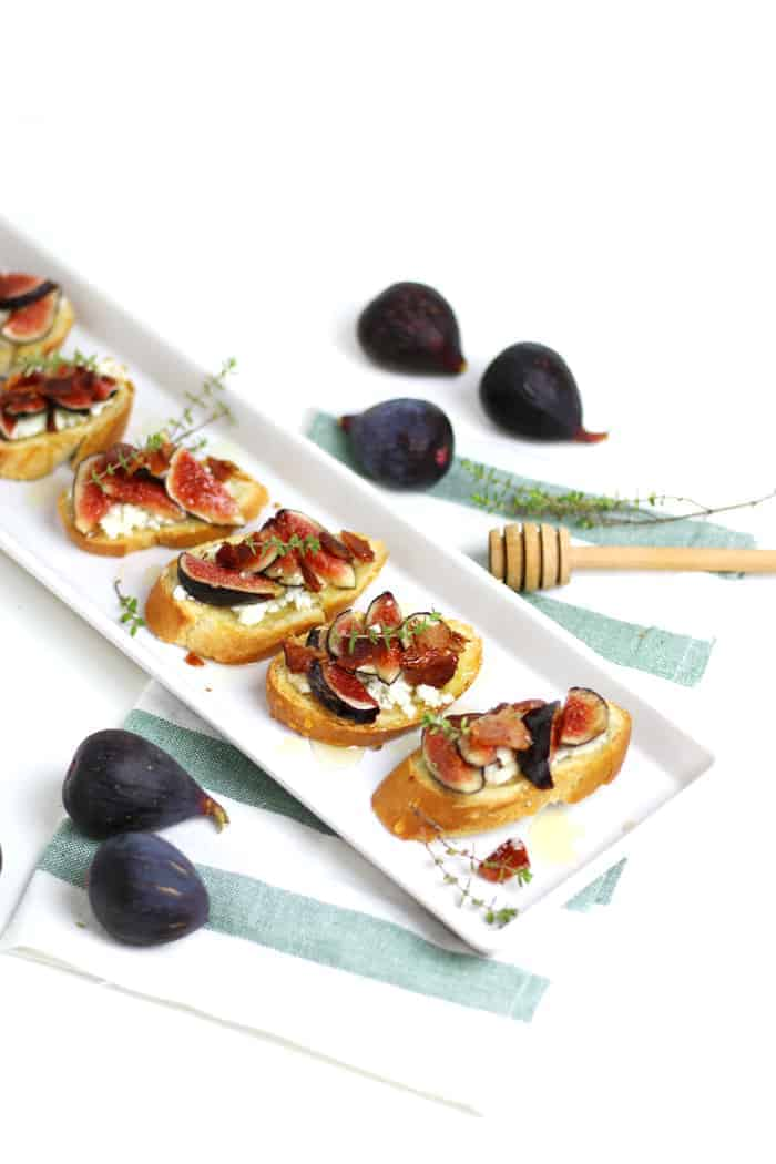 A platter of Fig, Goat Cheese, Bacon and Honey Crostini sit on a green and white striped towel, surrounded by whole figs
