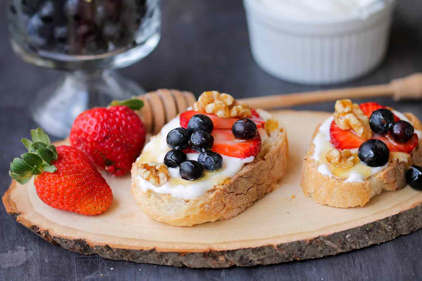 Whipped Cottage Cheese with Berries Crostini sit on a wooden serving platter, surrounded by strawberries, blueberries and honey