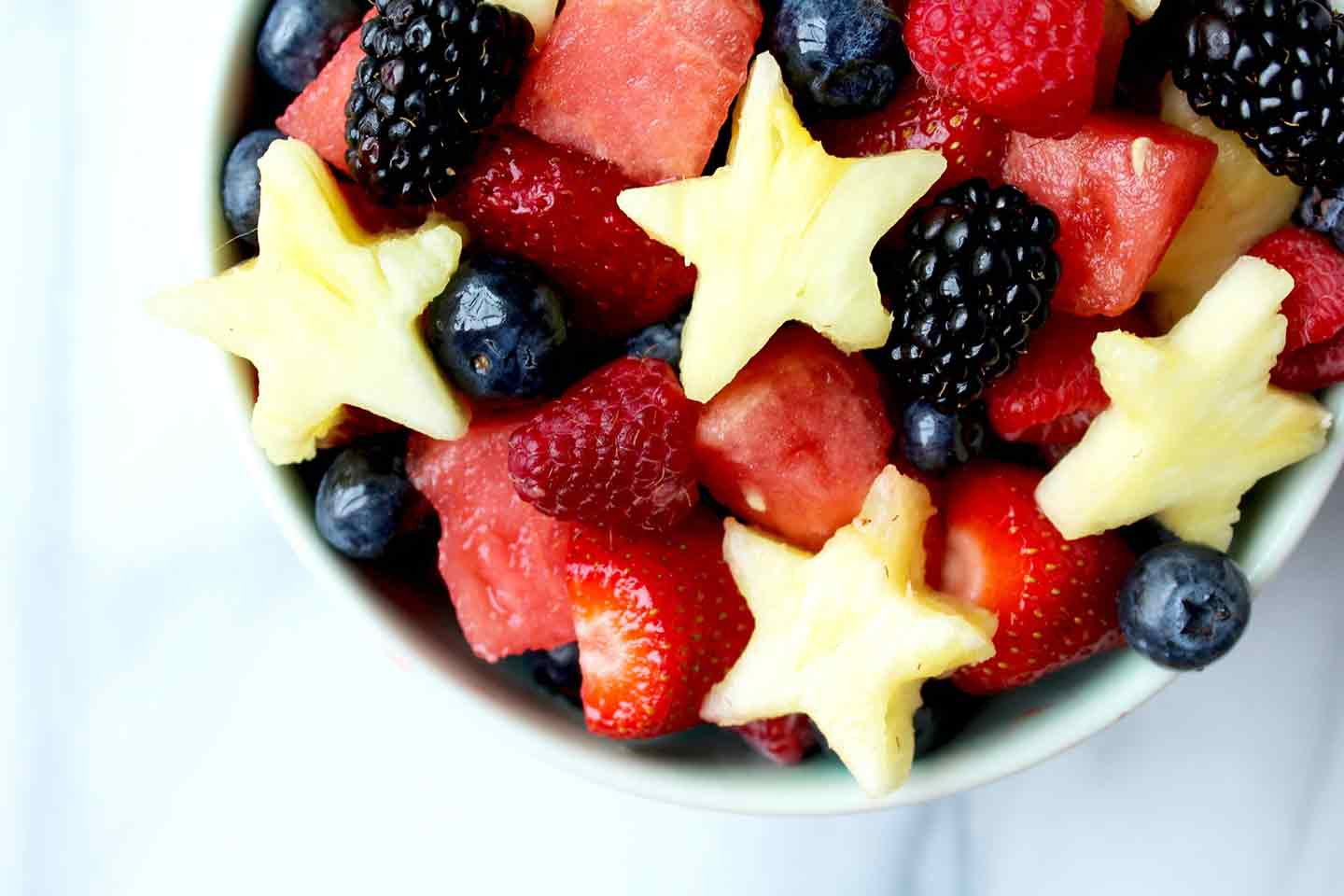 Close up of Red, White and Blue Fruit Salad from overhead, featuring strawberries, blackberries, blueberries, pineapple and watermelon