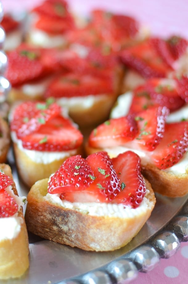 Several Strawberry Mascarpone Crostini sit on a silver platter before serving