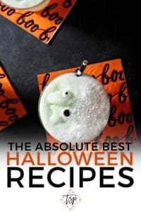 A Halloween drink--complete with monster eyes--sits on a black background with an orange napkin with Pinterest text
