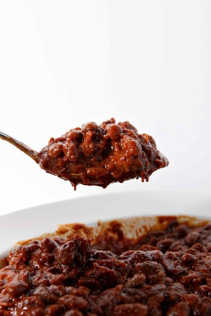 A spoon holds a scoop of Instant Pot Baked Beans