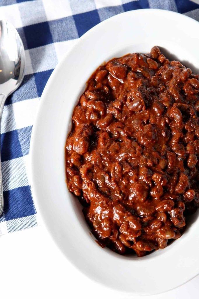 A white bowl of an easy baked beans recipe on a buffalo check napkin